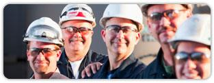 Smiling industry professionals wearing hardhats