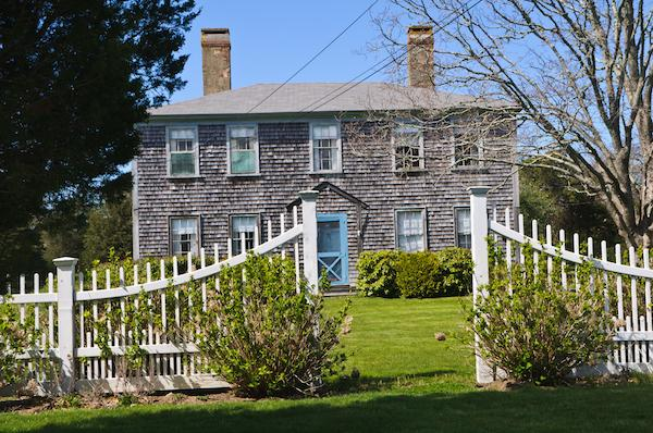 Old country house with green front lawn and fence
